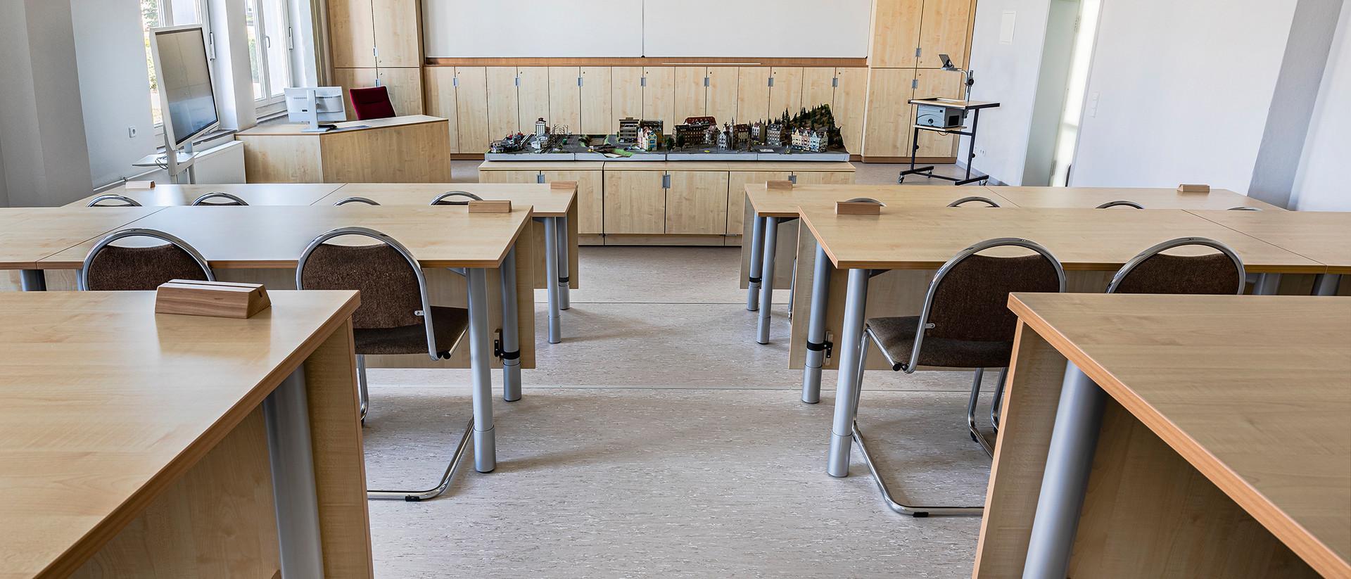 Ein leerer Hörsaal mit holzverkleideten Stühlen und Tischen.