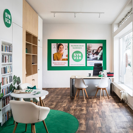 Zu sehen ist die Räumlichkeit der Firma Synvia mit Regalen, zwei Stühlen und einem Tisch.