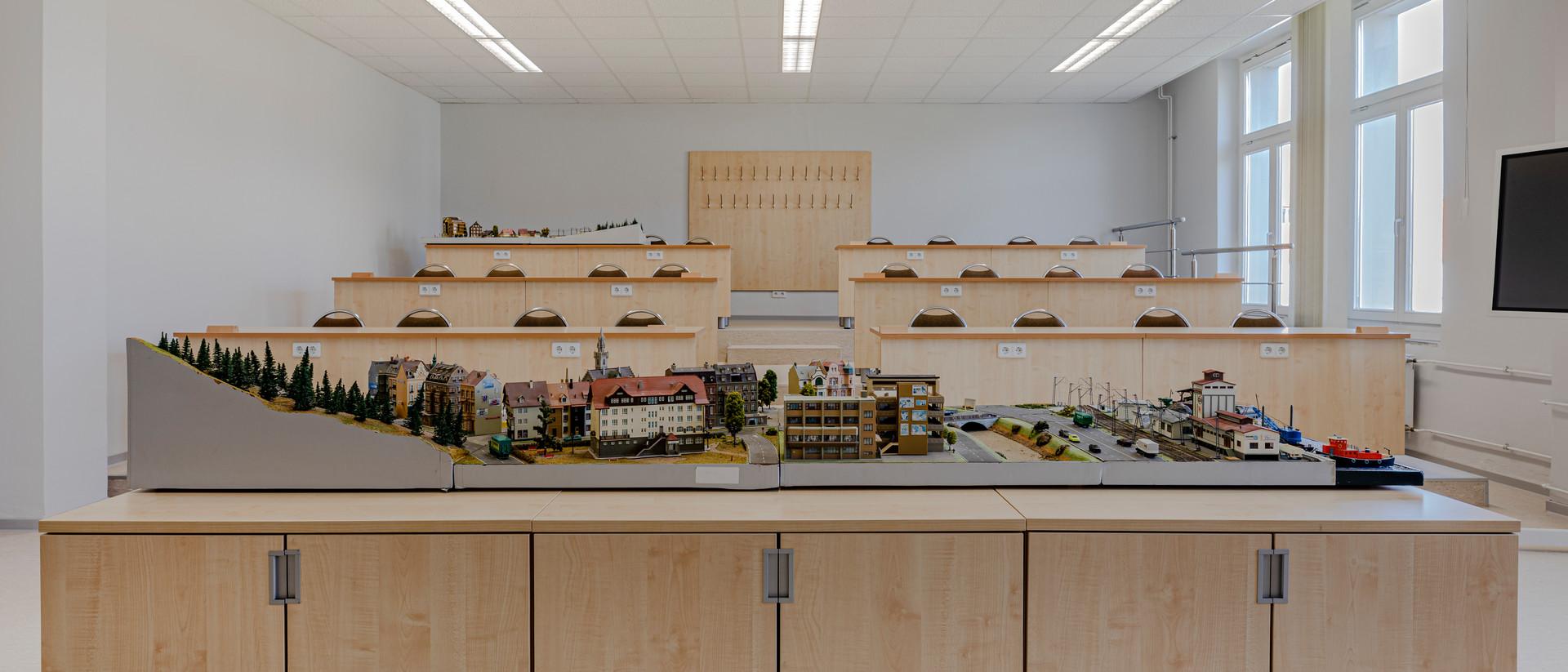 Ein leerer Hörsaal mit holzverkleideten Tischen. Im Vordergrund steht eine Miniatur modellierte Stadt.